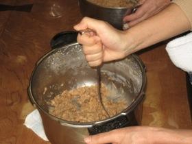 大豆をマッシャーでつぶす